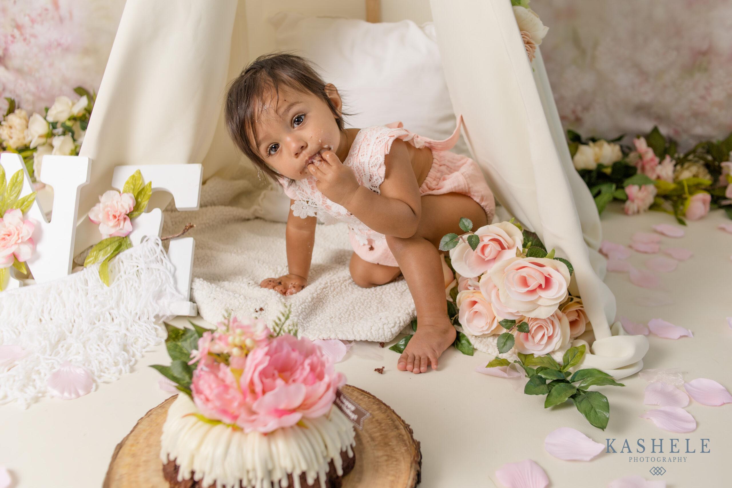 Little girl eating her cake during her milestone cake smash session