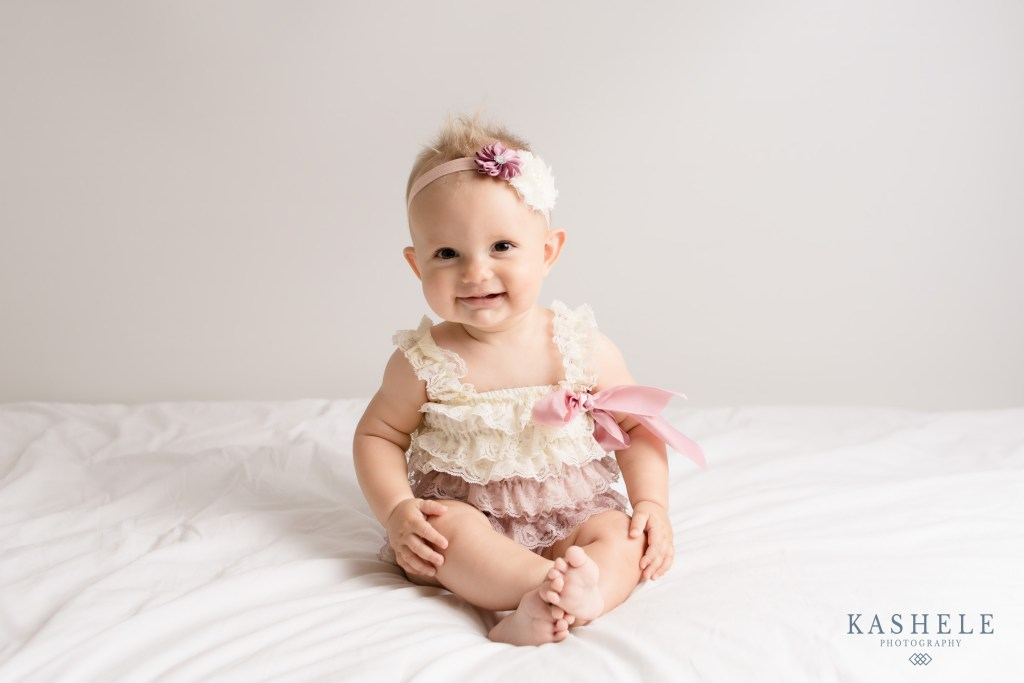 Smiling 6 month old girl during her milestone photography session
