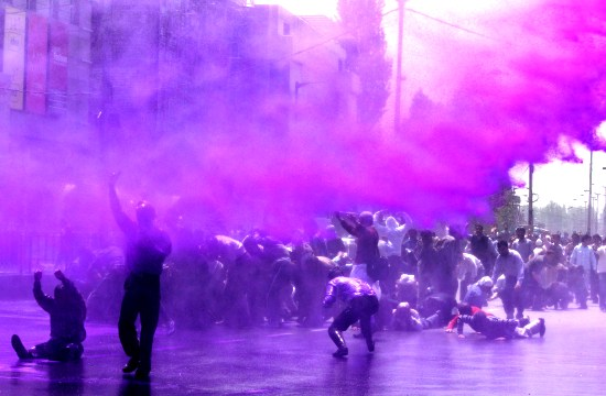 State government employees sprayed with colored water during protest in Srinagar. Photo by: Bilal Bahadur