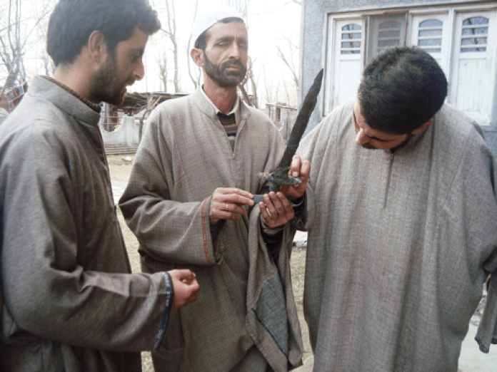 Ashraf(centre) with the dagger that he clamis to have found while digging for sand in Jehlum