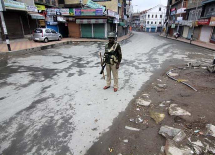 A CRPF personal patrolling a deserted street in Srinagar