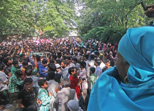 Women watch as procession carrying Shahnawaz's body is carried for burial in Dadsar village.