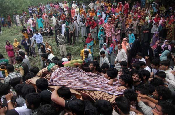 Women watch as procession carrying Shabir's body walks past in Hayena village in South Kashmir's Pulwama district.