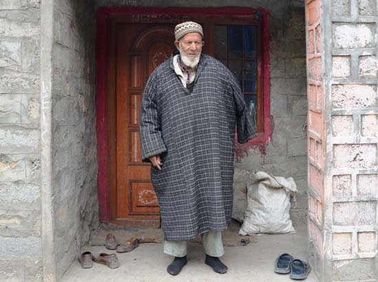 Ghulam Qadir Lone stands in  front of his house in Matayan