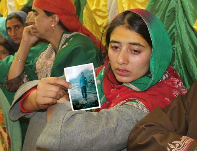 Sister of slain youth Tariq Ahmad Mir holding his picture  Photo: Waseem Muneeb