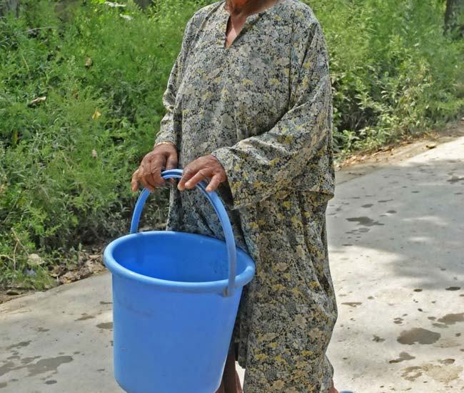 Bucketing water: This elder lady in Gund village is heading towards the community tap to fill her bucket with water.