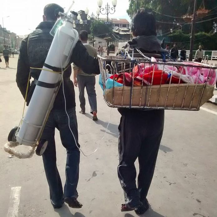 Two boys carrying a new born along with life support system. Photo Courtesy: FB