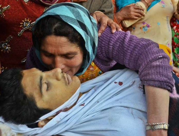 Goodbye: Sixteen-year-old Suhail Ahmad Sofi's mother kisses his dead body one last time before his funeral. Suhail was killed this morning when CRPF men fired on protestors during clashes in Central Kashmir's Narbal area.