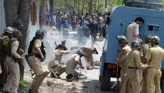 Policemen duck for cover as protestors pelt stones during clashes in Narbal.