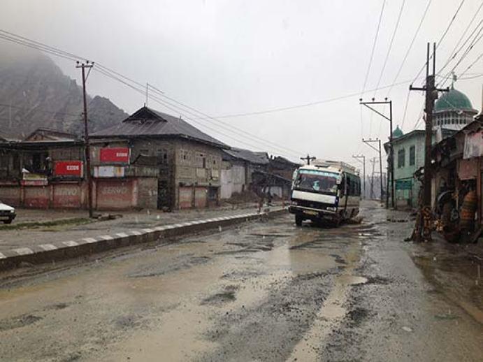 A passenger bus trying to wade through pot holed road to reach Srinagar.