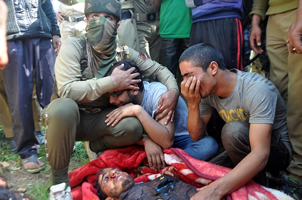 A policeman consoling brother of a slain militant in a South Kashmir police station. The slain militant had joined militant ranks barely a fortnight back. KL Image: Shah Hilal