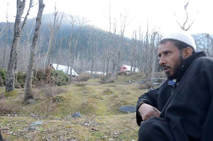 Ghulam Mohammad Bhat sitting in an orchard of unmarked graves in Kichama