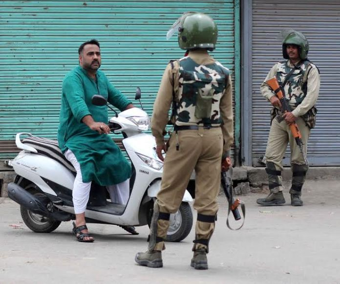 A Scooty rider being stopped by CRPF man inSrinagar as curfew continued in Kashmir on 8th consecutive day. (KL Image: Bilal Bahadur)