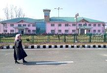 A girl walks outside deserted Dooru hospital building. KL Image by Shah Hilal