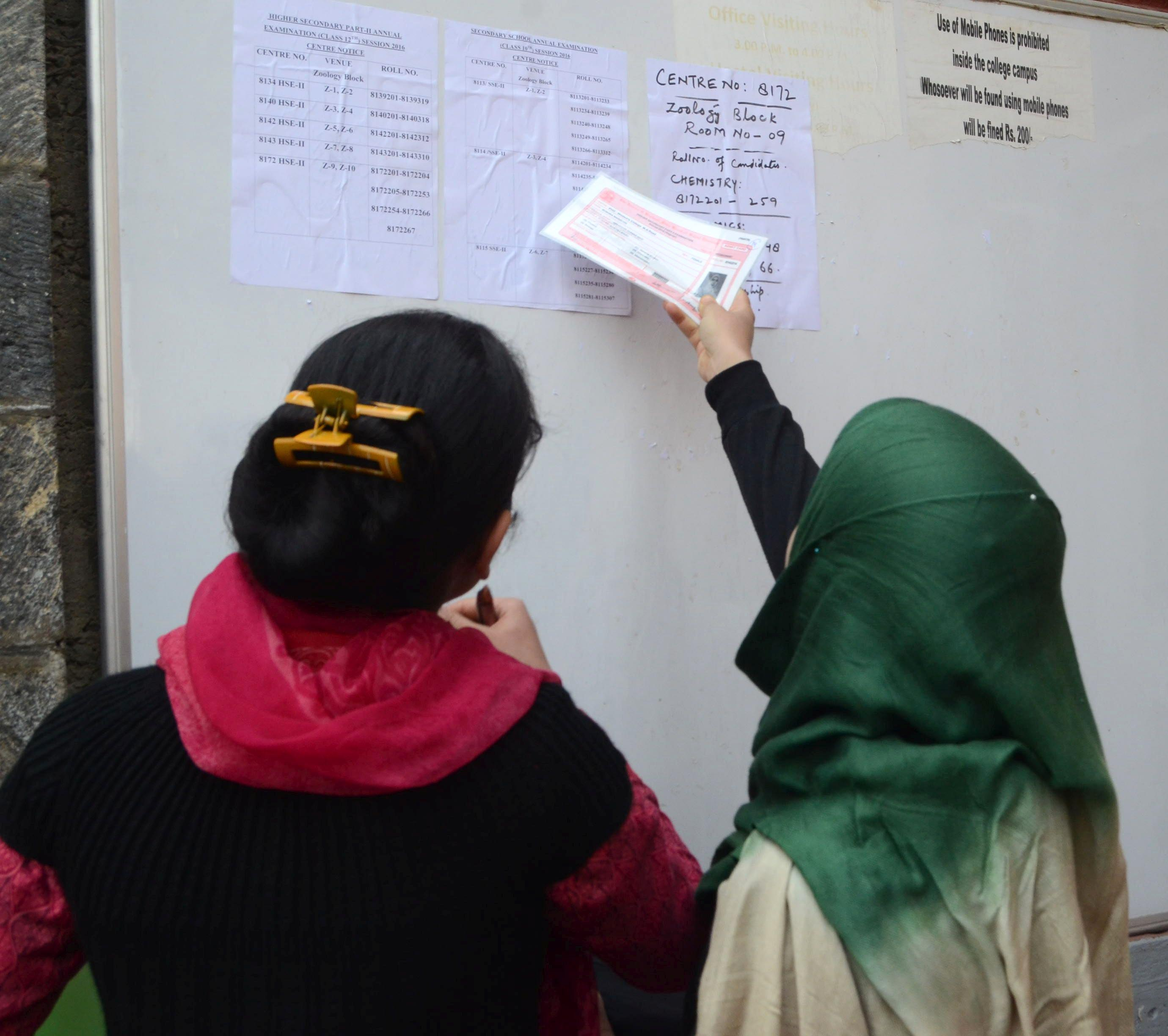 A student tries to locate her seat in the examination centre at Women's College, MA road, srinagar.