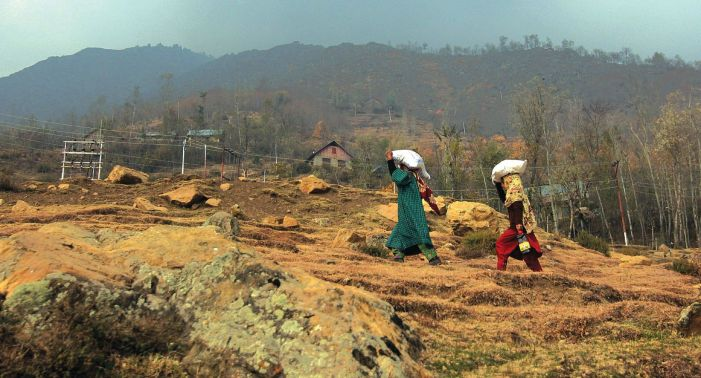 Women carrying stock on their back for winters as upper reaches remain mostly inaccessible due to accumulation of snow