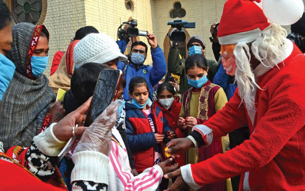 A man dressed as Santa Claus distributes sweets on Christmas Day in a church in Srinagar