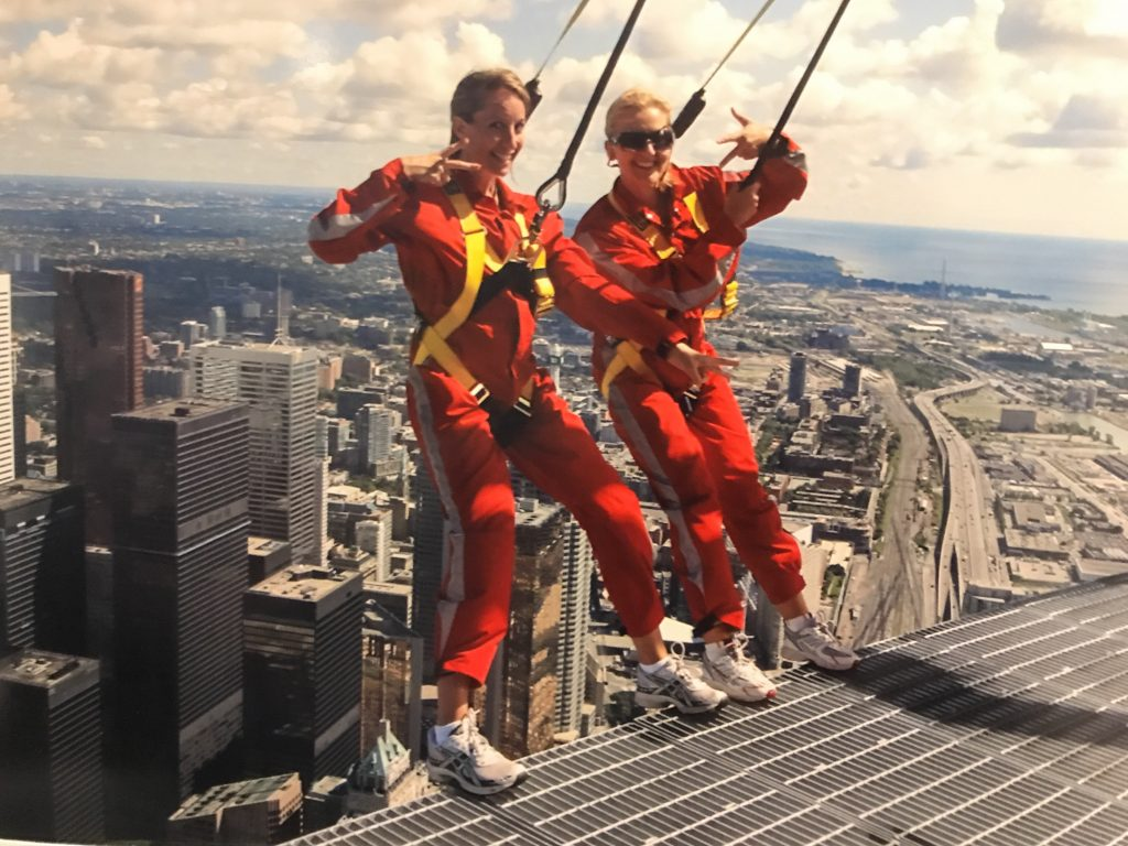 two women in jumpsuits on a platform overlooking Toronto