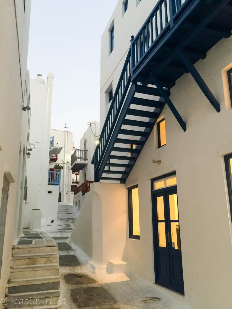 streets of mykonos with white houses and blue trim