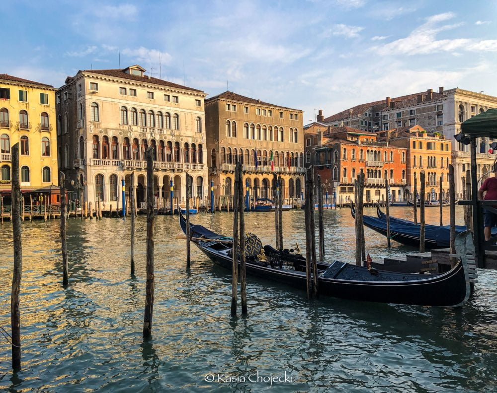 canal in Venice with parked gondola and mansions on water