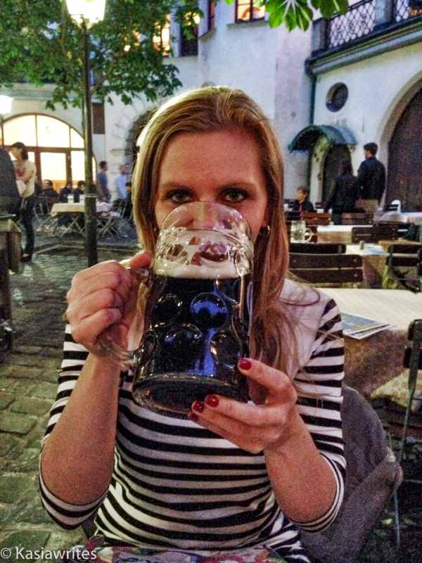 woman drinking dark beer out of a glass stein