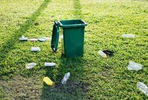 garbage on the ground around a green bin