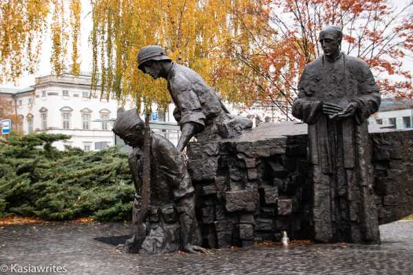 statue of soldiers with a priest overlooking