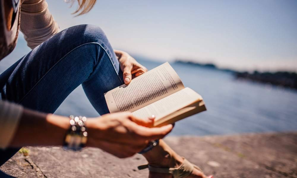 woman reading a book that can inspire travel by the lake