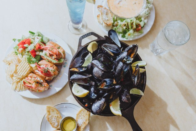 mussels in a dish with lobster rolls