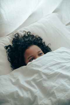ethnic child covering half of face with blanket lying in bed