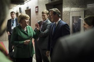 Chancellor Merkel and British Prime Minister David Cameron joke as they wait for their elevators after a European Council meeting in Brussels
