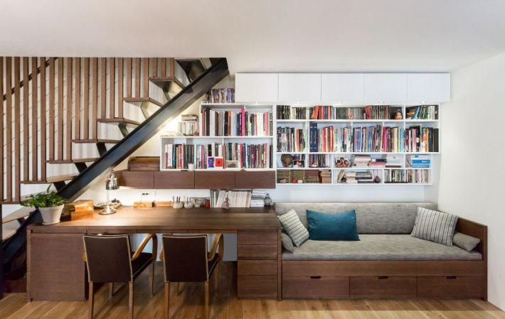 sous l'escalier une bibliotheque avec table et banquette, tout en bois sur mesure pour le sejour dans un apartement Parisien