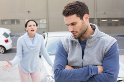 Young couple having an argument outside their car