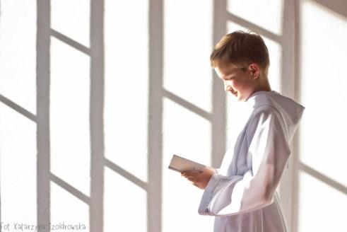 fotografia komunijna przedstawiająca chłopca czytającego książeczkę do nabożeństwa we wnętzru spowitymjasnym światłem. Zdjęcie wykonano w Krakowie Mistrzejowicach w kościele św. Maksymiliana Marii Kolbego