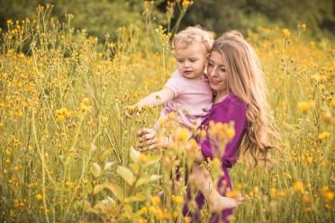 Plenerowa sesja fotograficzna matki z dzieckiem. Młoda matka z córeczką wśród pól pełnych żółtych kwiatów. Rodzinna Sesja fotograficzna wykonana w Krakowie