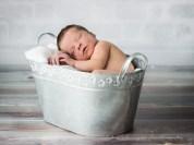 Fotografia noworodka osiedle Złotego wieku. Noworodek chłopczyk śpi w metalowej wanience.Newborn photographer Cracow