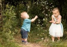 Fotografia dziecięca, sesja plenerowa. Rodzeństwo dziewczynka i chłopczyk bawią sięw łapanie baniekmydlanych.Fotografięwykonał fotograf dziecięcy w Krakowie Nowa Huta,Mistrzejowice