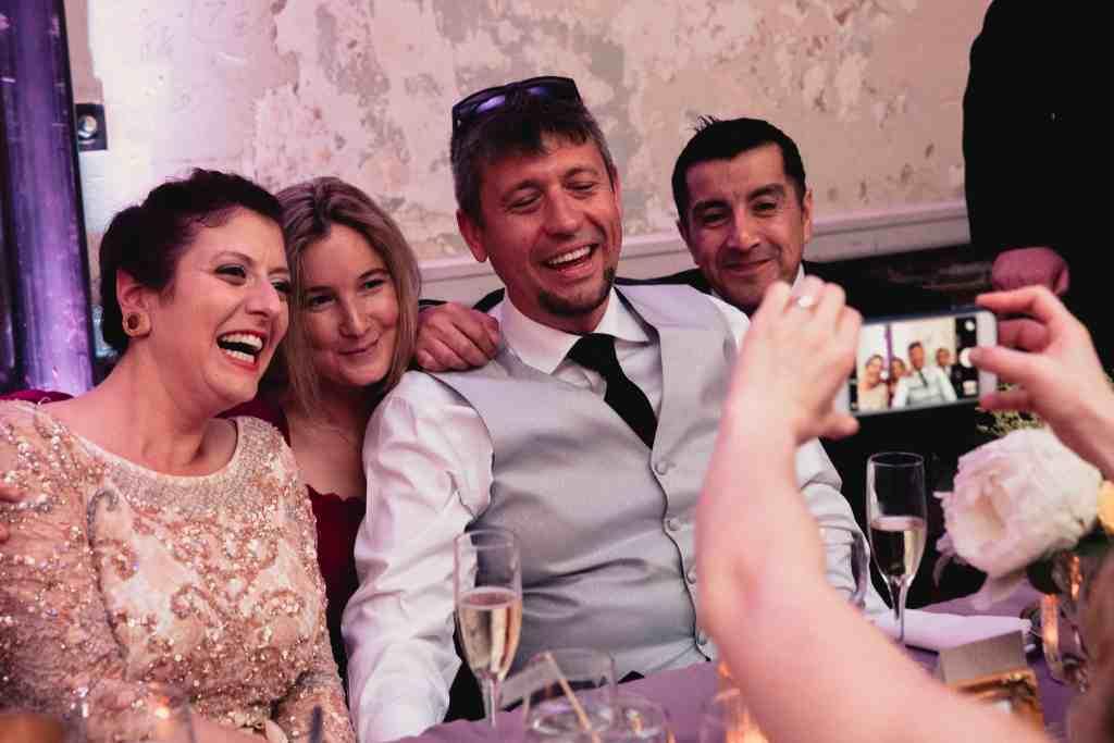 bride and groom having photo taken with guests at unique wedding venue