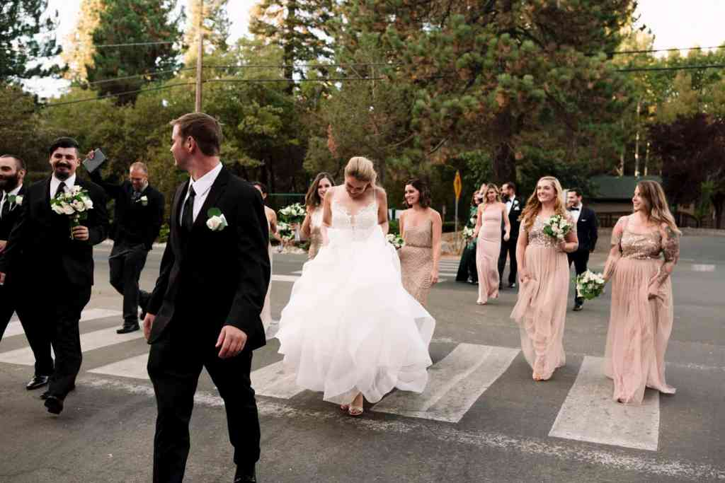 wedding party crosses road to lake