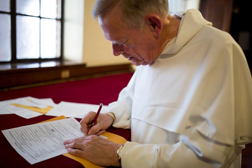 Priest signing the register