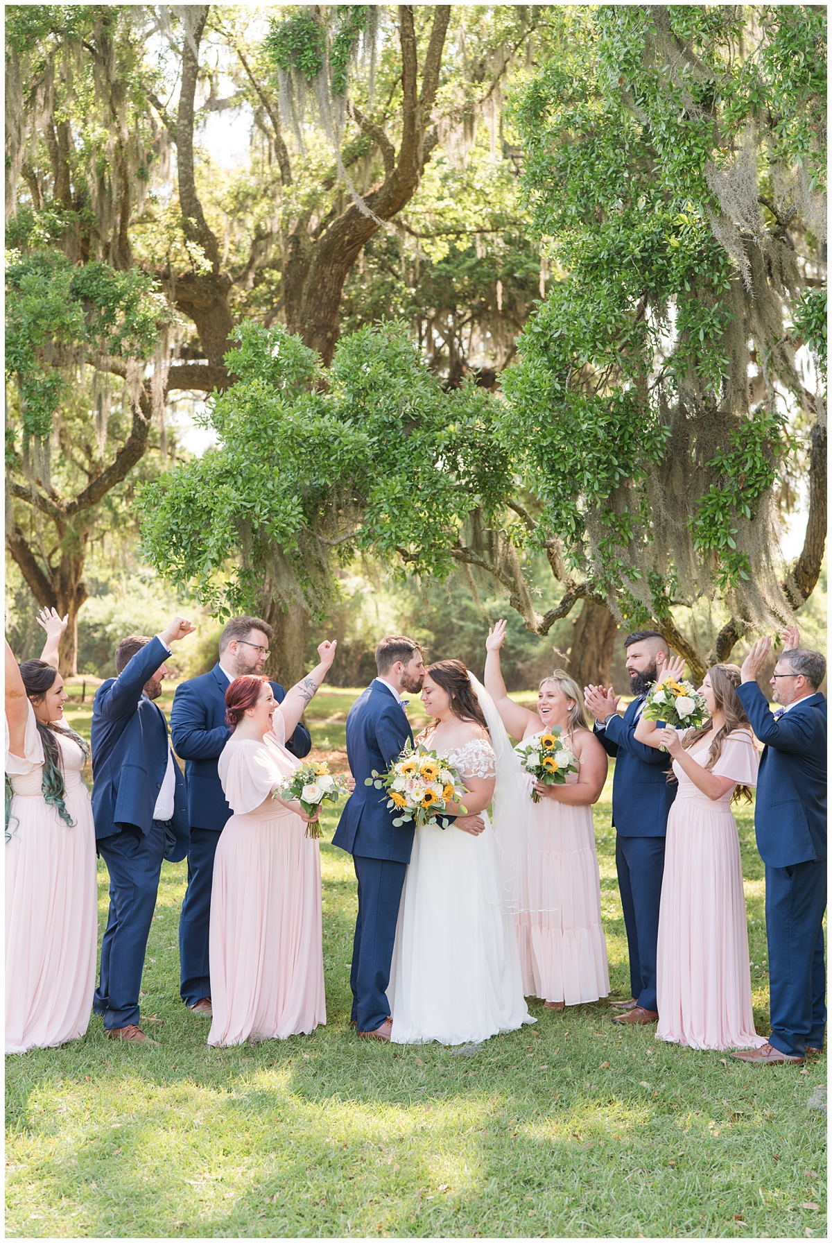 bridal party cheers while newlyweds kiss during Boone Hall wedding photos