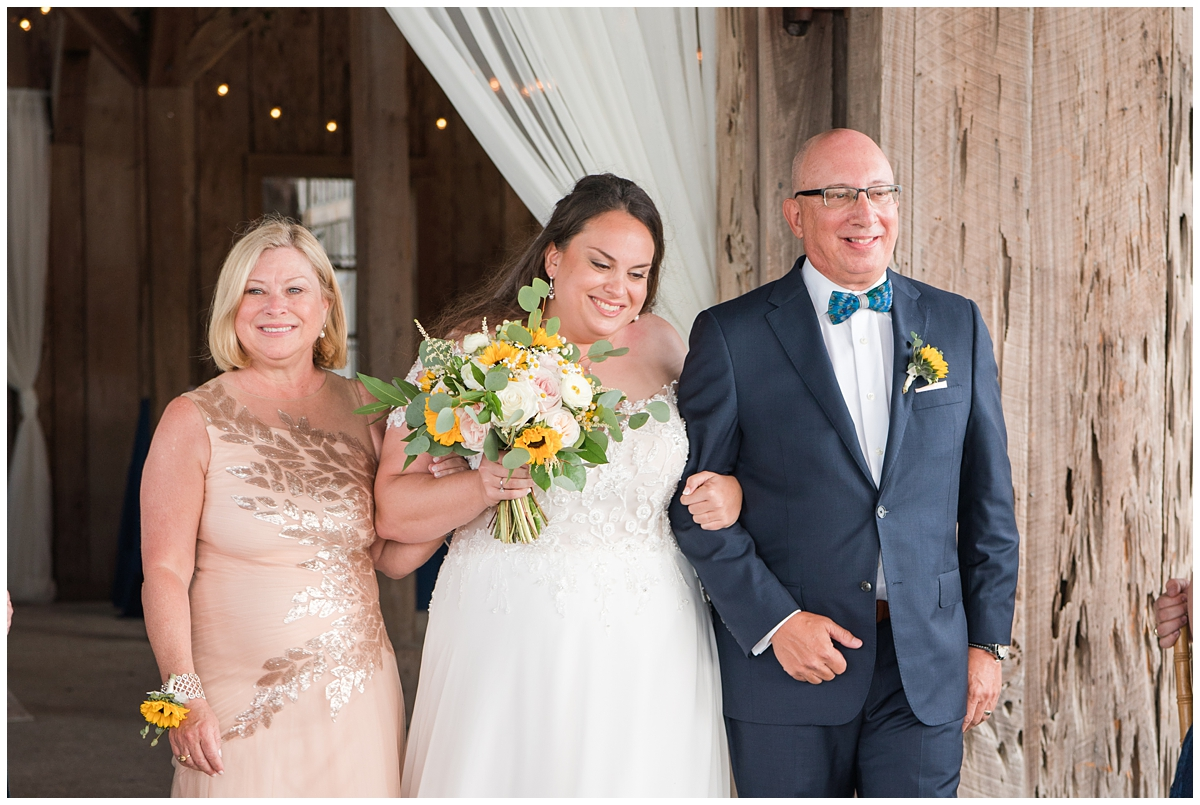bride walks down the aisle with parents at Boone Hall