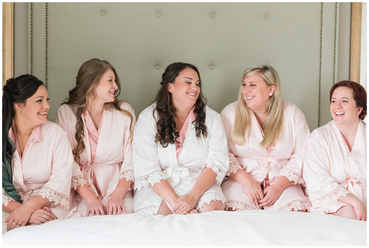 bride poses with bridesmaids in light pink robes before Boone Hall wedding