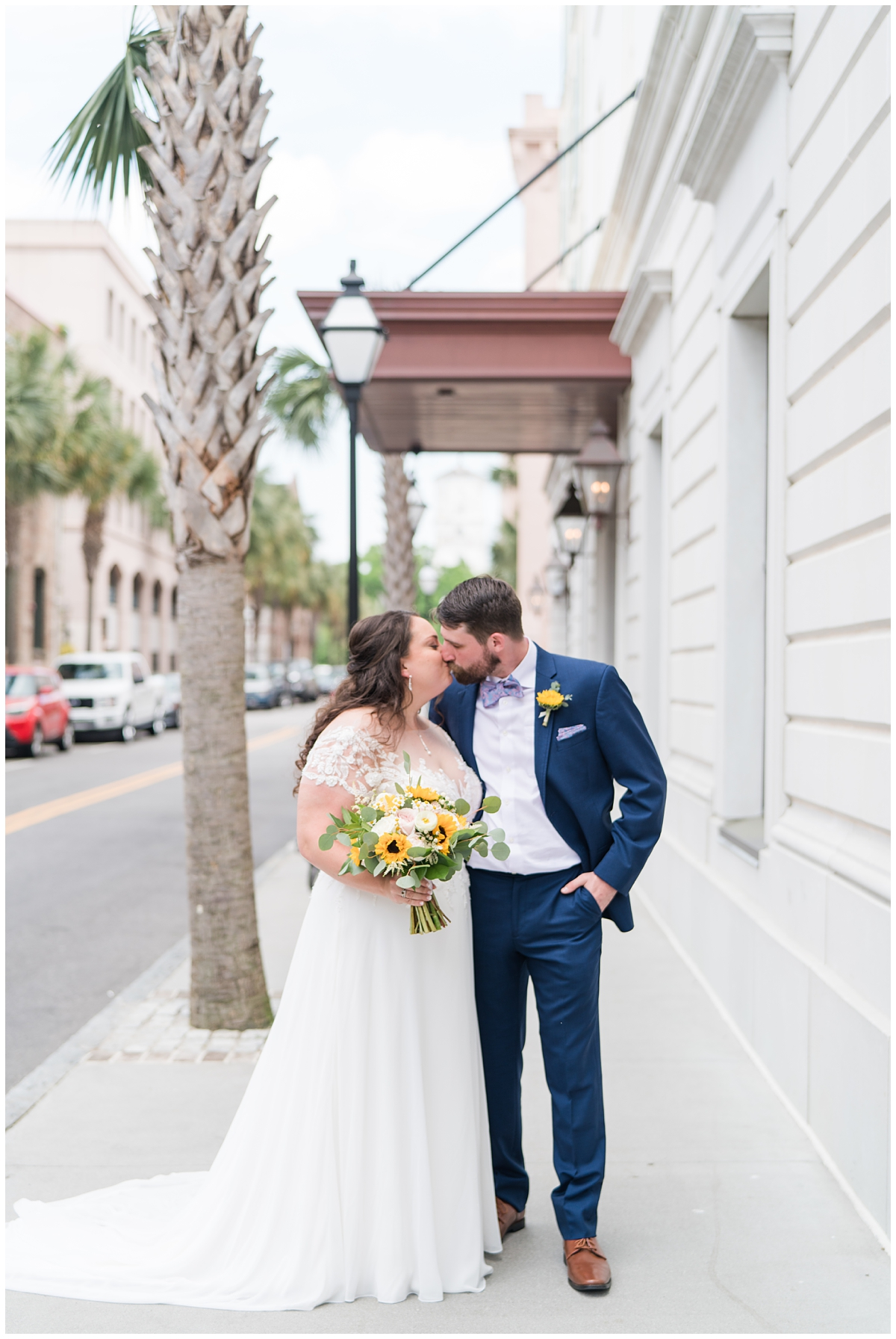 bride holding bouquet with sunflowers kisses groom in navy suit