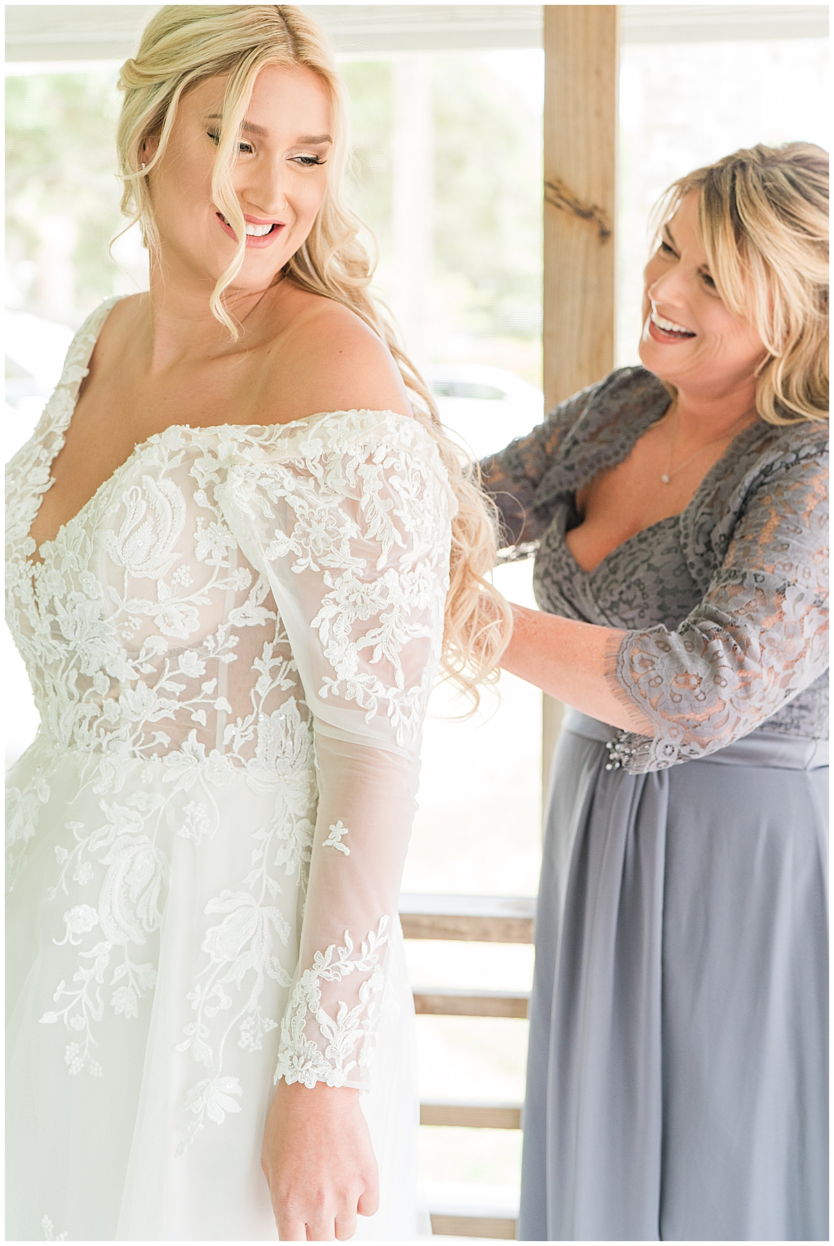 mother helps bride with wedding dress before Charleston wedding