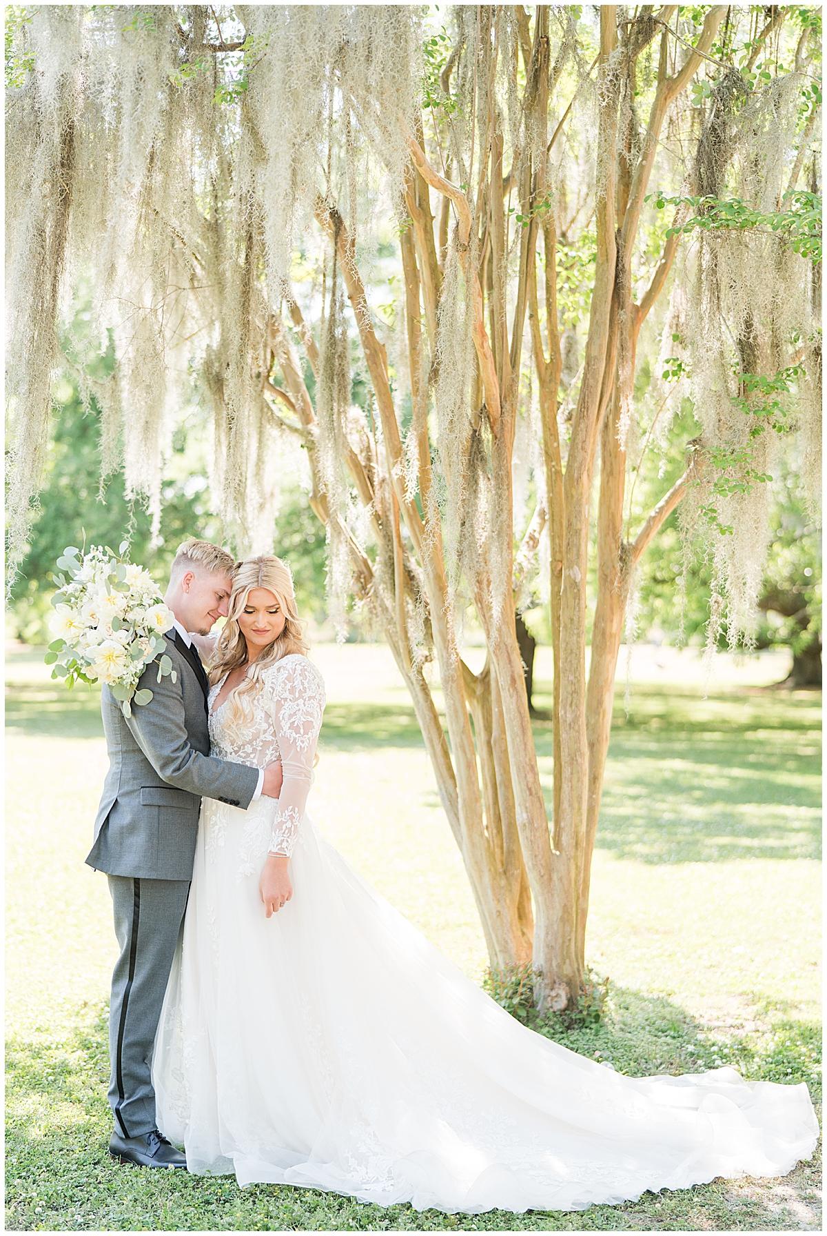 bride and groom hug by tree in downtown Charleston