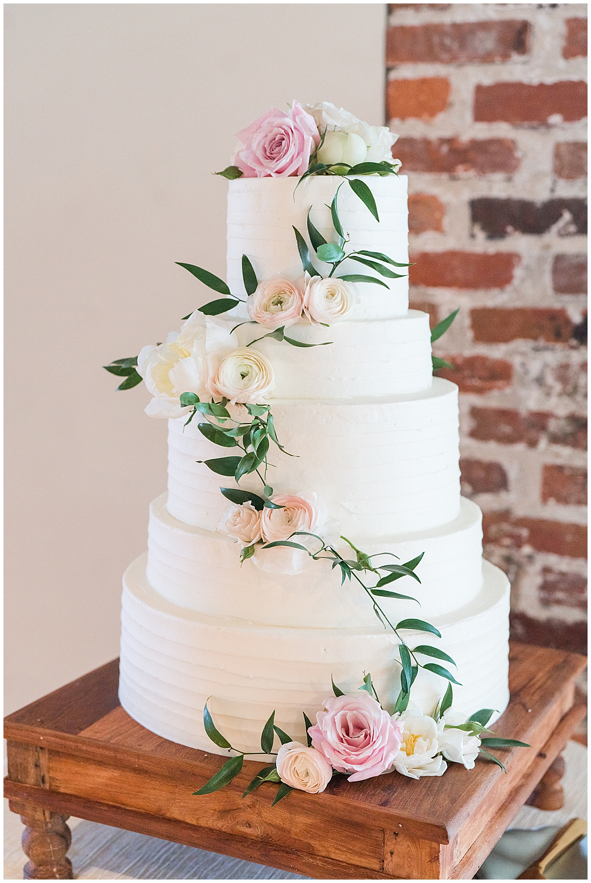 tiered wedding cake with winding leaves