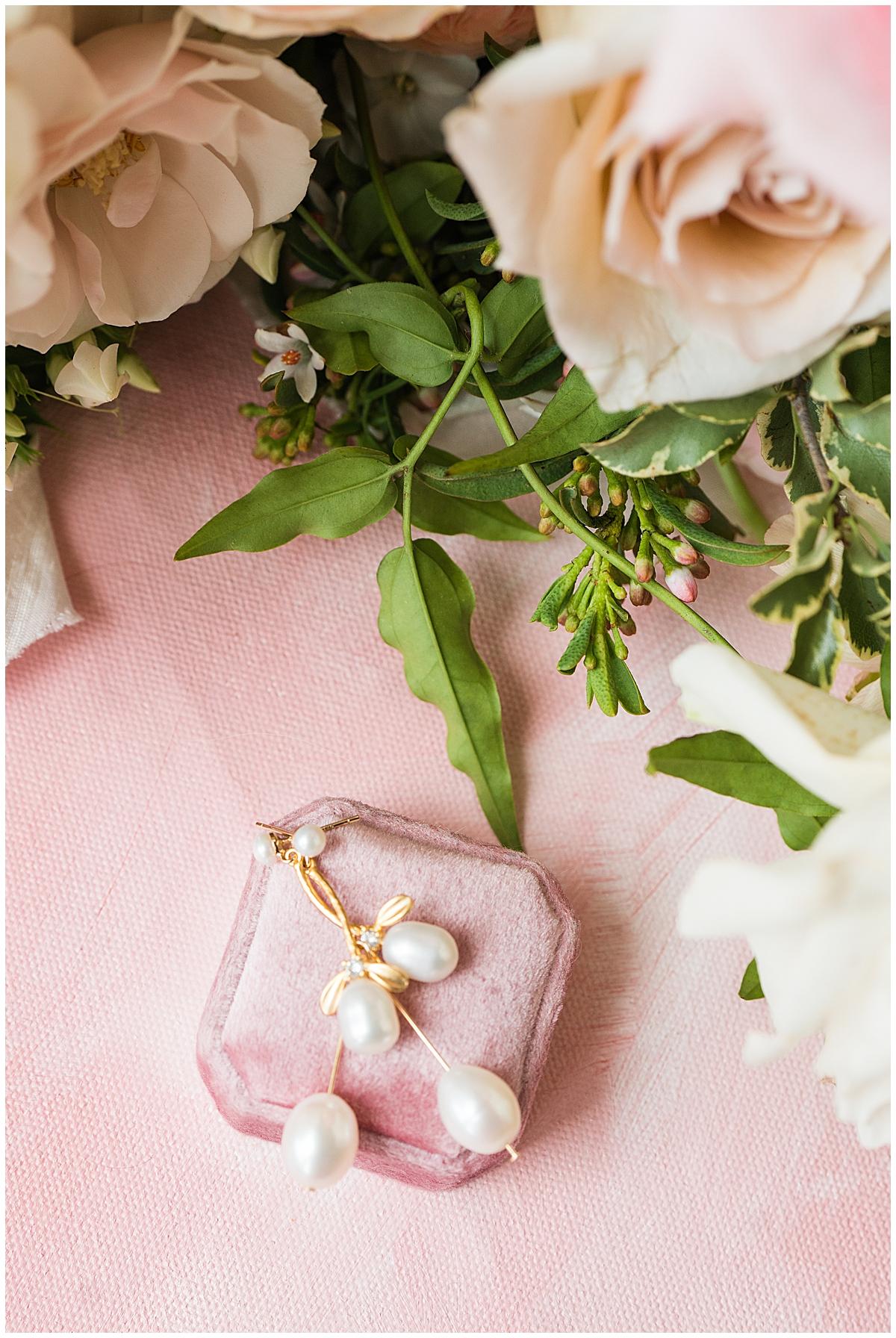 bride's jewelry on pink ring box before Charleston wedding