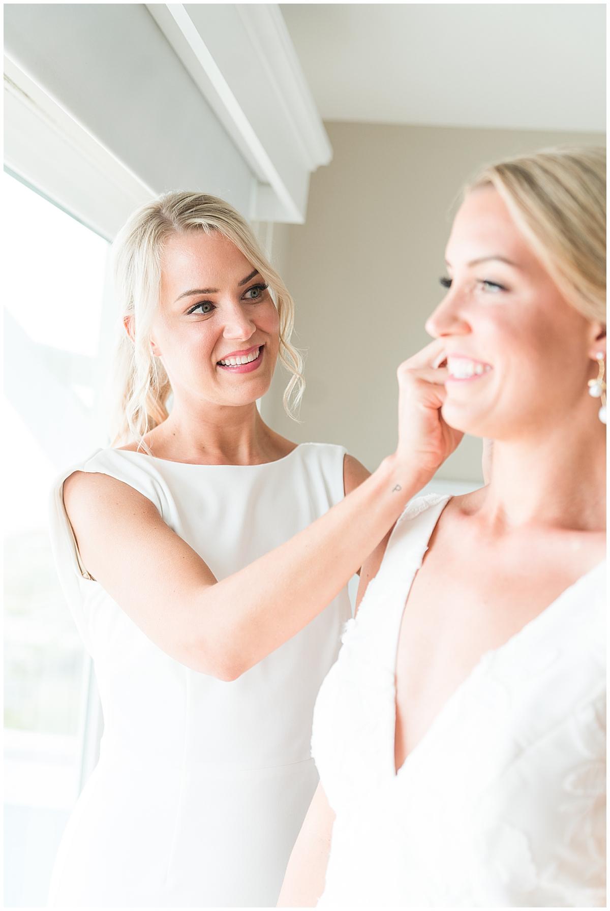 sister helps bride with earrings