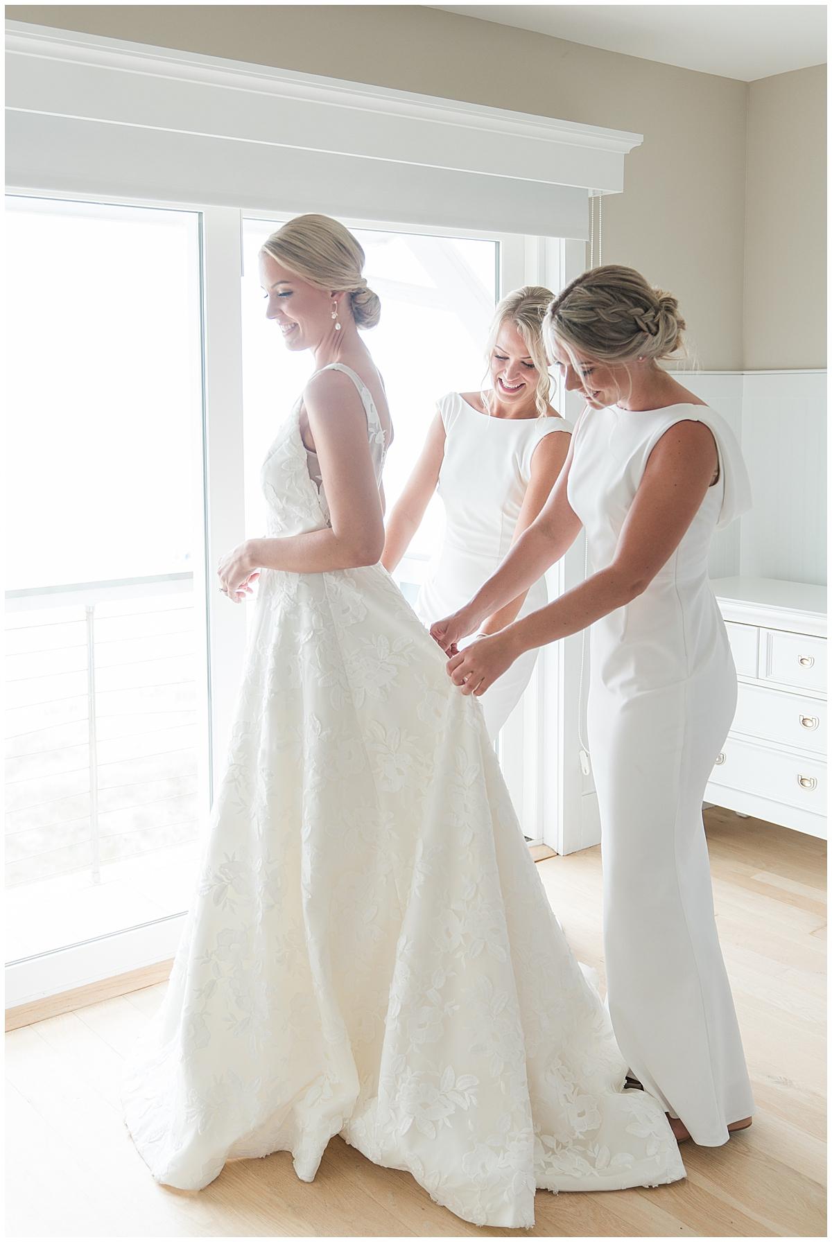 sisters help bride with wedding dress before Cedar Room Charleston wedding